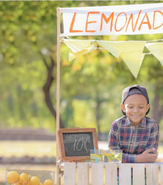 little boy sitting at his lemonade stand