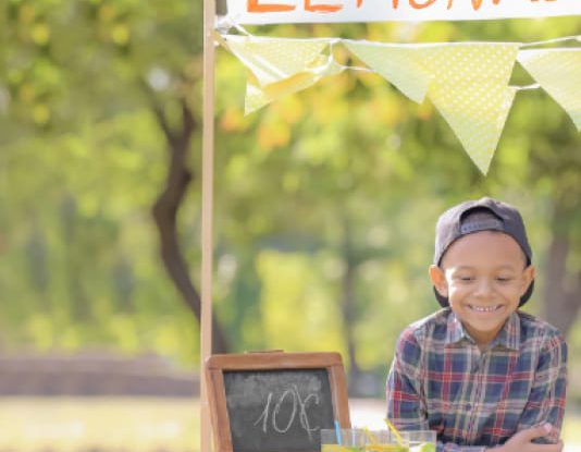 little boy smiling at his lemonade stand