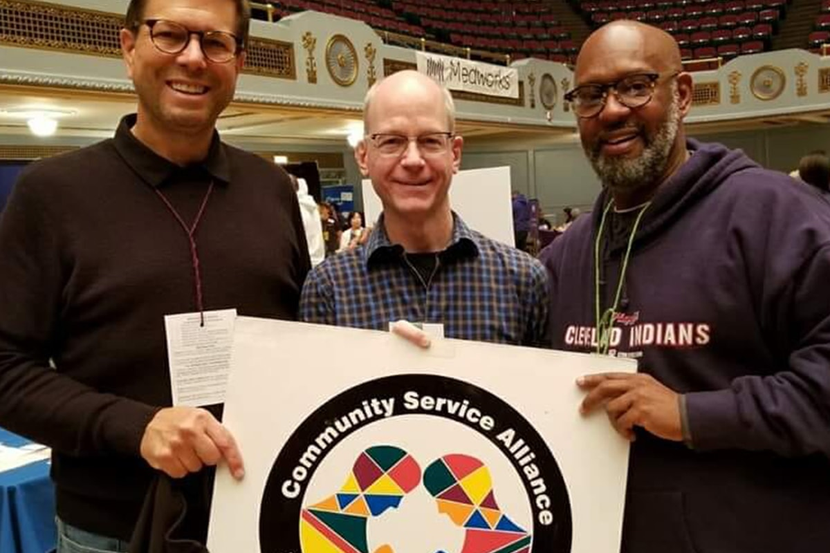 "three gentleman holding a ""Community Service Alliance"" sign"