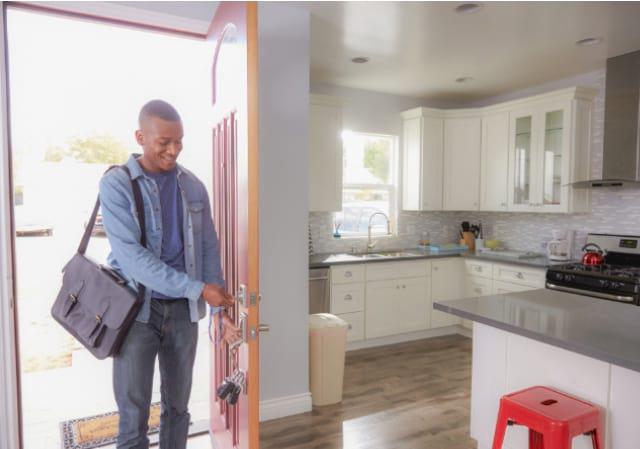 gentleman unlocking his front door to his house